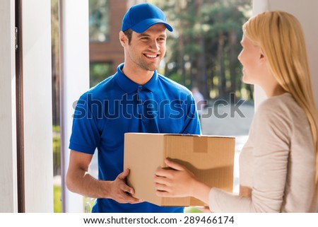 Fast and reliable service. Cheerful young delivery man giving a cardboard box to young woman while standing at the entrance of her apartment - stock photo