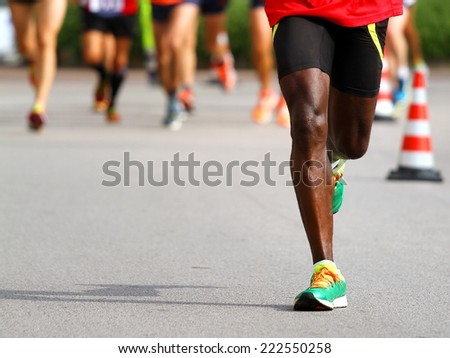 fast athlete runs down the street during the race outdoors - stock photo