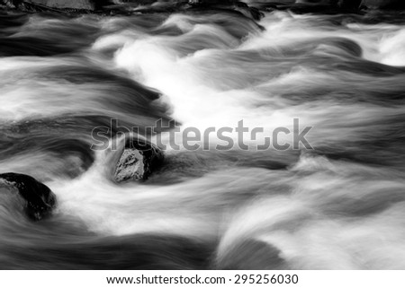Fast flowing mountain stream and rocks  - stock photo