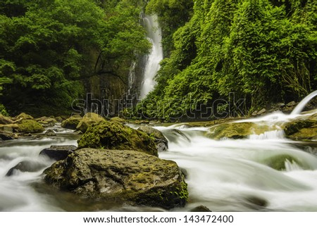 Fast flowing mountain stream in Costa Rica with a waterfall in the background. - stock photo