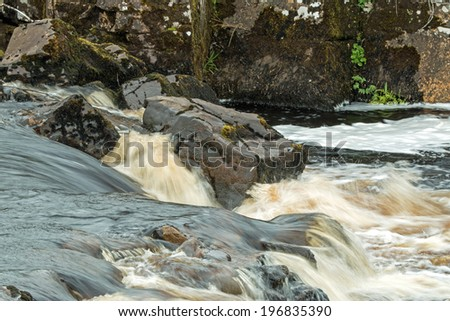 Fast-flowing peat-water river on The Isle of Skye, Scotland - stock photo