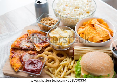 fast food and unhealthy eating concept - close up of fast food snacks and coca cola drink on wooden table - stock photo