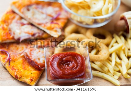 fast food and unhealthy eating concept - close up of ketchup in glass bowl over pizza, deep-fried squid rings, potato chips, peanuts and ketchup on wooden table - stock photo