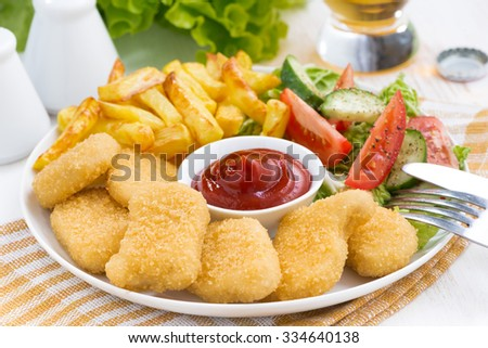 fast food - chicken nuggets, french fries and vegetable salad, closeup - stock photo