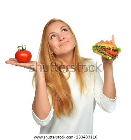 Fast food concept. Tasty unhealthy burger sandwich in hand and tomato getting ready to eat isolated on a white background - stock photo
