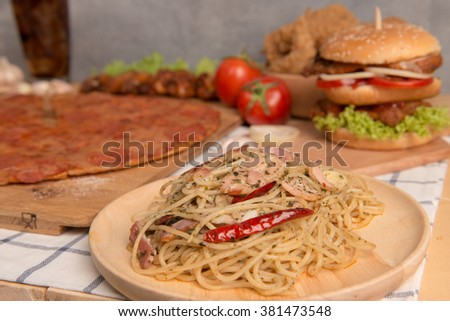 Fast food concept with spaghetti , fried chicken , pizza and burger as a symbol of diet temptation resulting in unhealthy nutrition - stock photo