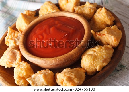 Fast food: crispy popcorn chicken fillet with sauce close-up on a plate. horizontal - stock photo