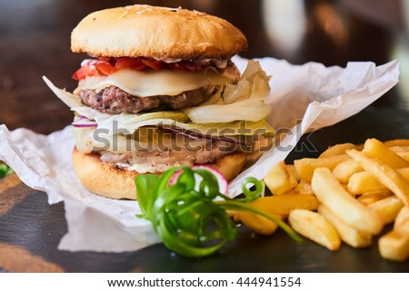 Fast food dinner of Burger and fries, served on a stone Board