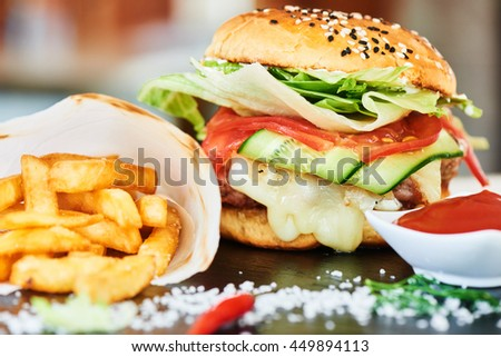 Fast food dinner of Burger, fries and a Cup of sauce, served on a stone Board