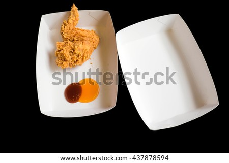 Fast food fried chicken on paper dish isolated on black background - stock photo