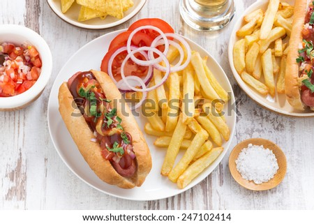 fast food - hot dog with French fries and chips, top view, horizontal - stock photo
