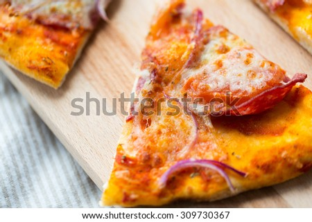 fast food, italian kitchen and eating concept - close up of homemade pizza slice on wooden table