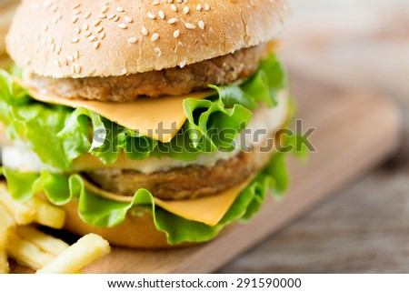fast food, junk-food and unhealthy eating concept - close up of hamburger or cheeseburger on table - stock photo