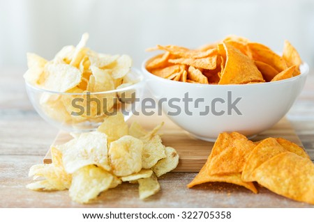 fast food, junk-food, cuisine and eating concept - close up of crunchy potato crisps and corn crisps or nachos in bowls - stock photo