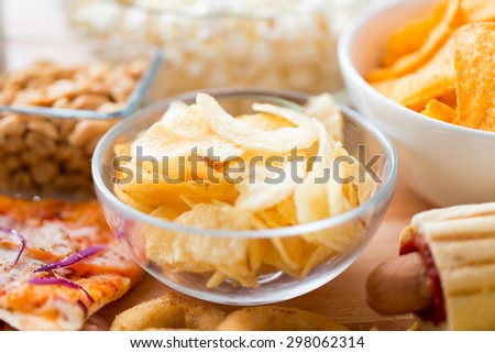 fast food, junk-food, cuisine and eating concept - close up of crunchy potato crisps in glass bowl and other snacks - stock photo