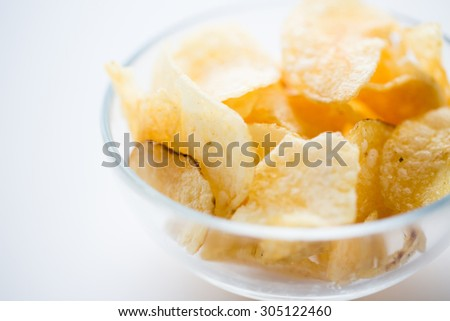 fast food, junk-food, cuisine and eating concept - close up of crunchy potato crisps in glass bowl - stock photo