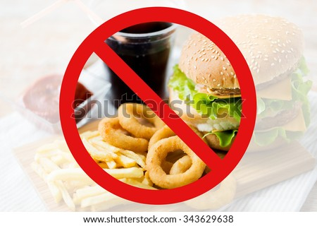 fast food, low carb diet, fattening and unhealthy eating concept - close up of hamburger or cheeseburger, deep-fried squid rings and french fries behind no symbol or circle-backslash prohibition sign - stock photo