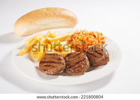 Fast food menu - meatballs, salad and french fries in a plate