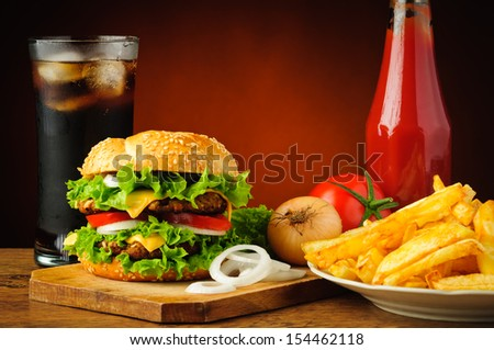 fast food menu with big tasty hamburger, vegetables, french fries, tomato ketchup and cola drink - stock photo