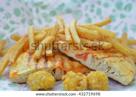 Fast food on the paper - french fries potato, sandwich and chicken nugget