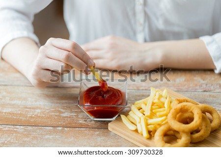 fast food, people and unhealthy eating concept - close up of hands with deep-fried squid rings, dipping french fries into ketchup bowl on wooden table - stock photo