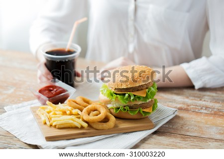 fast food, people and unhealthy eating concept - close up of woman hands with hamburger or cheeseburger, french fries, squid rings and cola drink sitting at table - stock photo