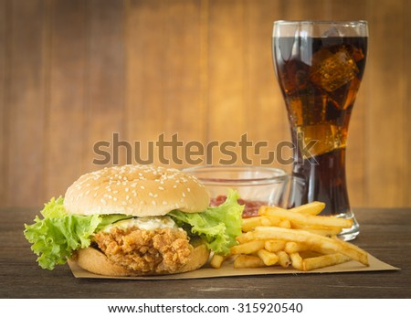 fast food set hamburger and french fries with cola on wood background. - stock photo
