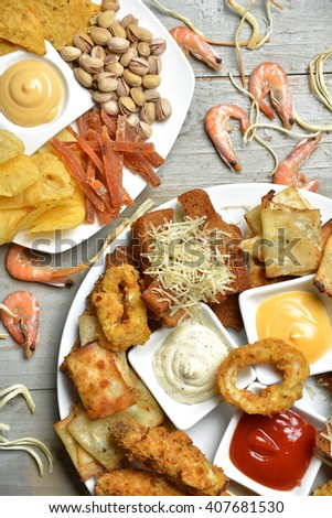 Fast food snacks composition with text copy pistachios nuts dried salty fish strips and croutons with cheese chicken nuggetson rustic wood background. Unhealthy junk food - stock photo