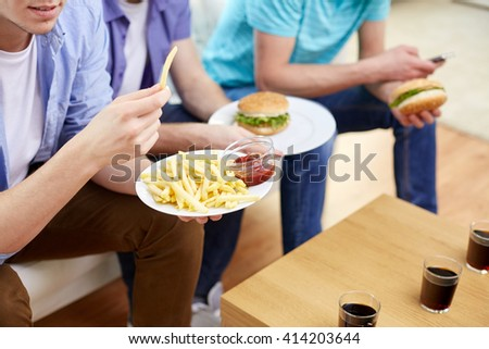 fast food, unhealthy eating, people and junk-food - close up of happy friends eating french fries and hamburgers at home