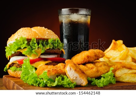 fast food with burger or cheeseburger, chicken nuggets, french fries and cola drink - stock photo