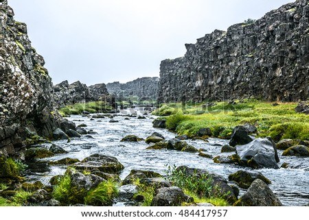 Fast icelandic stream surrounded by high rocks and green grass in summer