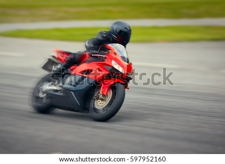 Fast motorbike racing on the race track at high speed. Composite image with heavy image editing.