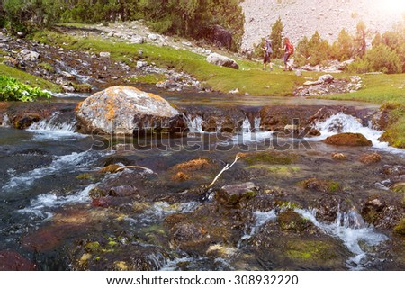 Fast mountain creek. Rapid water stream of river on foreground and group of people hiker walking up hill footpath on background with bright sun shining - stock photo