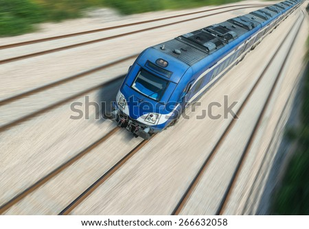 Fast moving blue train, blurred background - stock photo