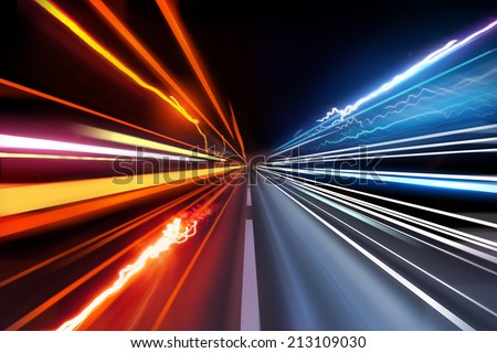 Fast moving traffic light trails at night. - stock photo
