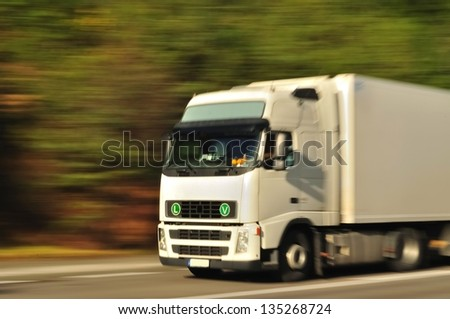 Fast moving white truck, motion blur - stock photo