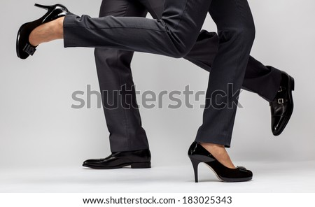 Fast-paced business: male and female legs running on grey background