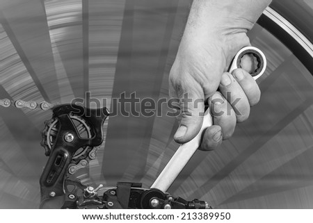 fast repair of a bicycle with a metal wrench - stock photo