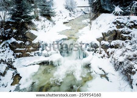 Fast river with waterfall in Austrian Alps at snowy day - stock photo