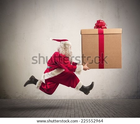 Fast runner Santa Claus with a big present - stock photo