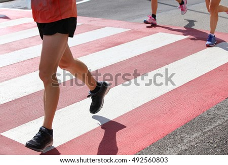 fast runners during a marathon race in the city on a pedestrian crossing withstripes red and white