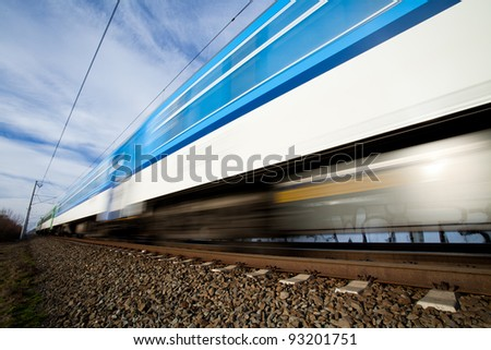 Fast train passing under a bridge on a lovely summer day (motion blurred image) - stock photo