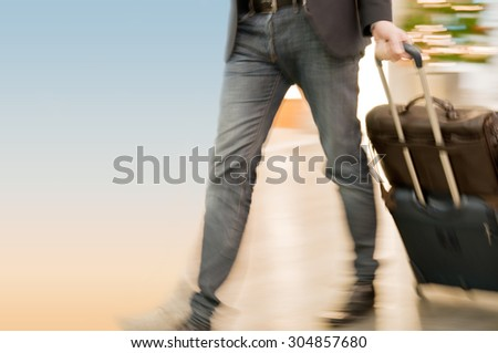 Fast walking businessmen in an airport building - stock photo