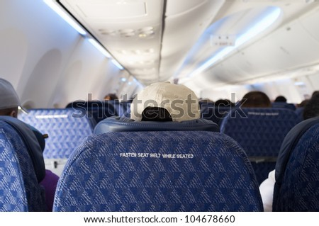Fasten seat belt sign on the back of a seat from a commercial airliner. - stock photo