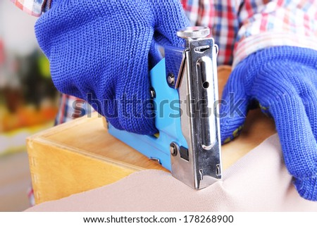 Fastening fabric and wooden box using construction stapler close up - stock photo