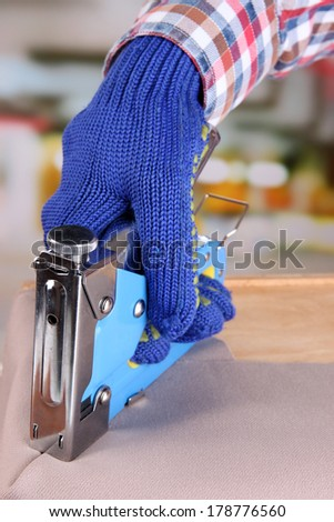Fastening fabric and wooden box using construction stapler on bright background - stock photo