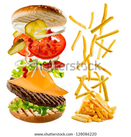 Fastfood - hamburger and french fries - flying fried potatoes and flying ingredients of hamburger - stock photo