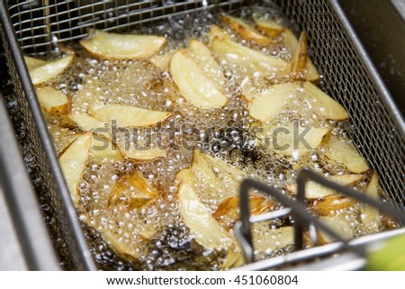 Fastfood kitchen - potatoes frying  in the oil in the fritter - stock photo