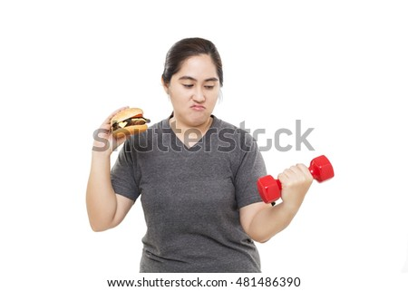 Fat Asian woman holding a burger and dumbbell isolated on white background. Hesitate.
