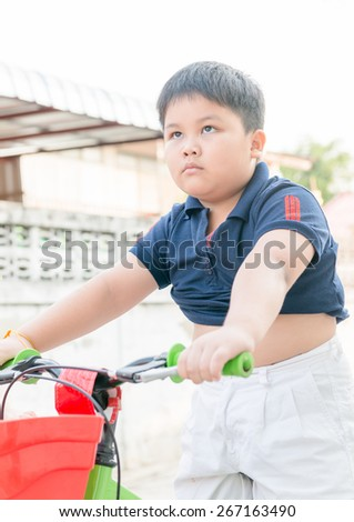 fat boy engrossed to lose weight by ride bicycle - stock photo